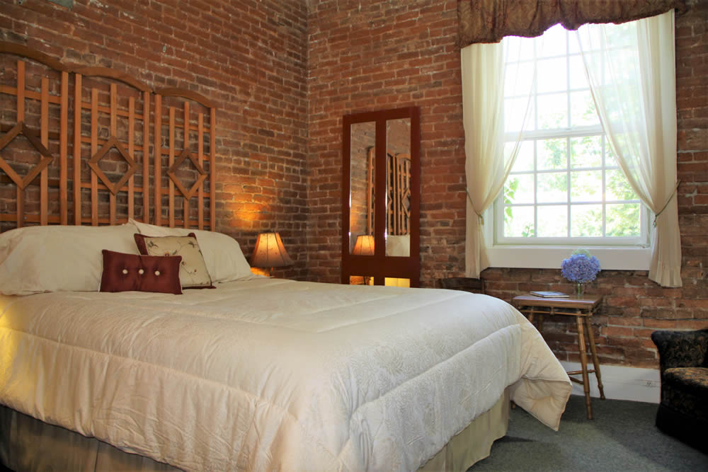 Amador Hotel Guest Room with bed and brick wall