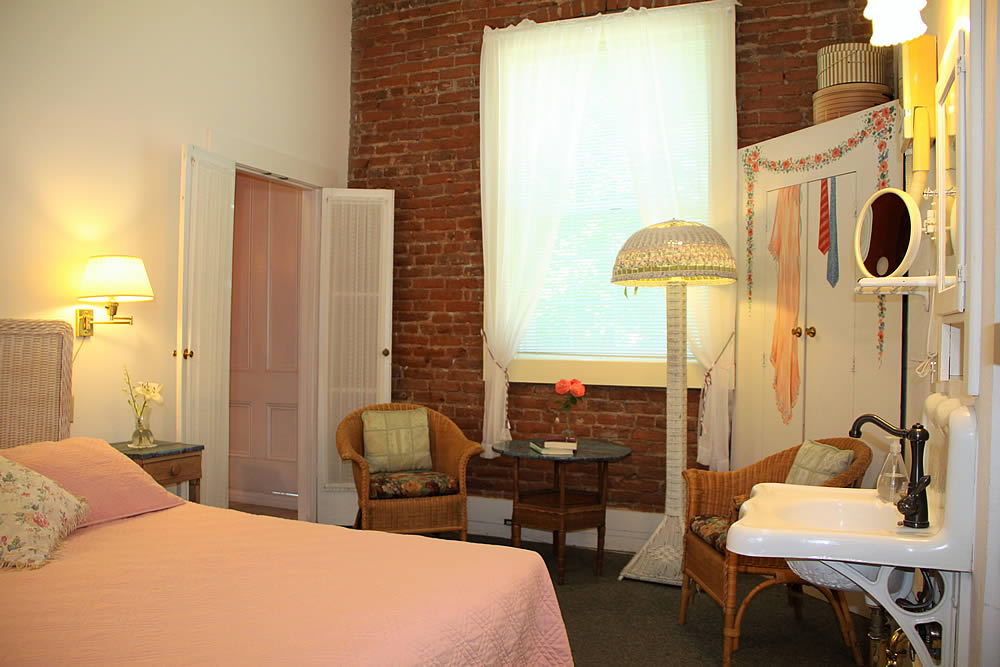Amador Hotel Guest Room with bed and chairs with brick wall